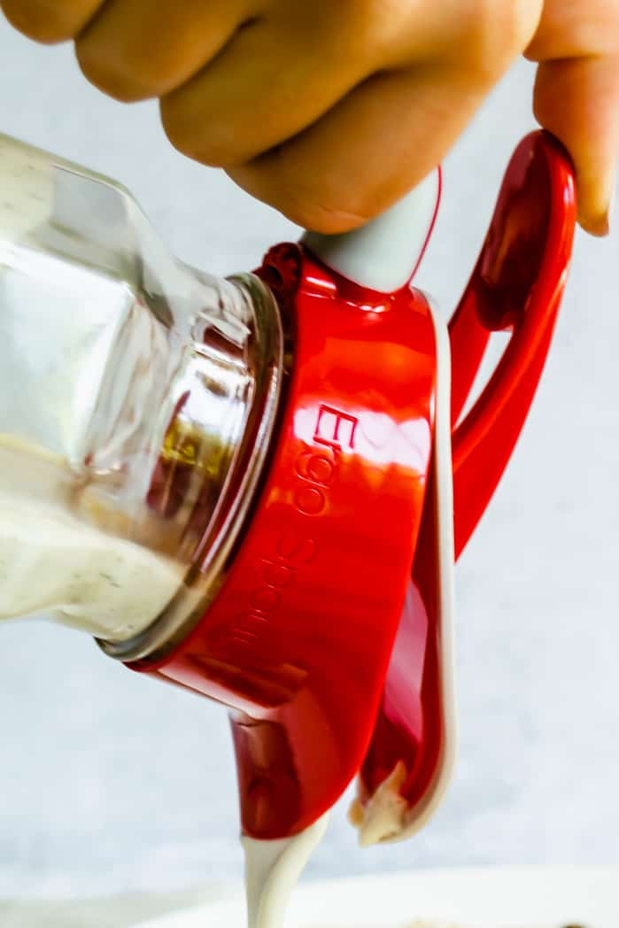 close up of hand pouring salad dressing with an ergo spout on a mason jar