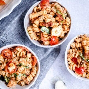 three white bowls with pasta salad on a gray napkin.