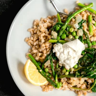 white dish with farro, English peas, asparagus and spinach with lemon and a white towel