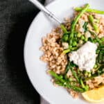 white dish with farro, English peas, asparagus and spinach with lemon and a white towel.