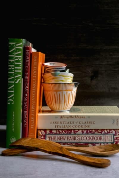 close up of five cookbooks on a black and white background with wooden spoons and decorative measuring cups