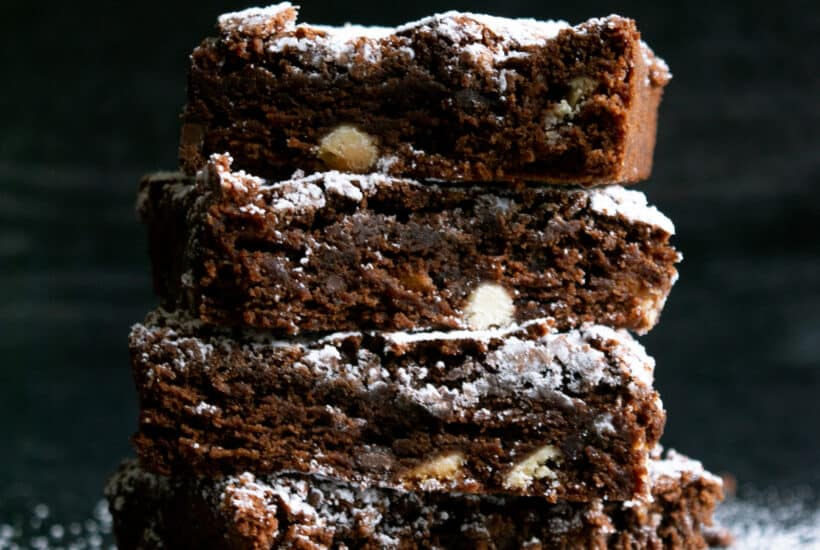 stack of five brownies with powdered sugar on a dark background