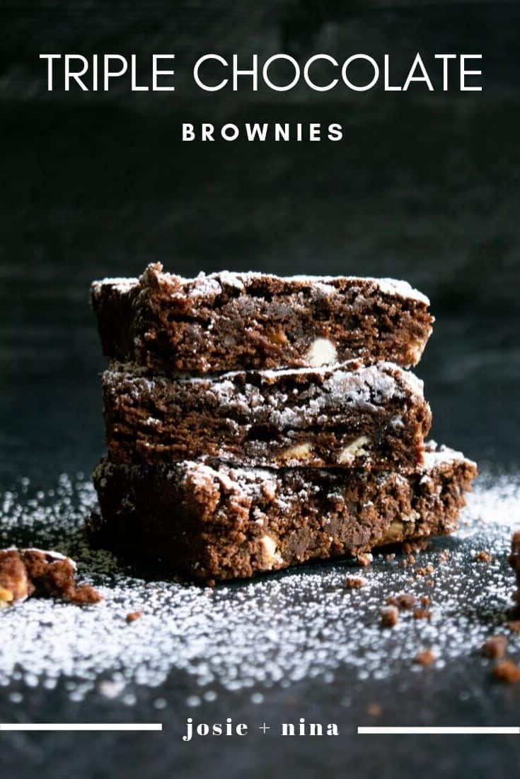 three brownies stacked on top of each other with powdered sugar in front of a black background