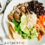 authentic carnitas in a bowl with black beans, rice, peppers and guacamole.