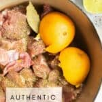 Authentic carnitas in a dutch oven with oranges and bay leaves.