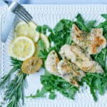 sous vide chicken with lemon and roasted garlic on a white platter with utensils and a gray napkin.