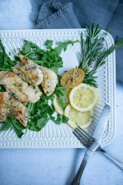 sous vide chicken with lemon and roasted garlic and rosemary on a white platter with utensils and a gray napkin