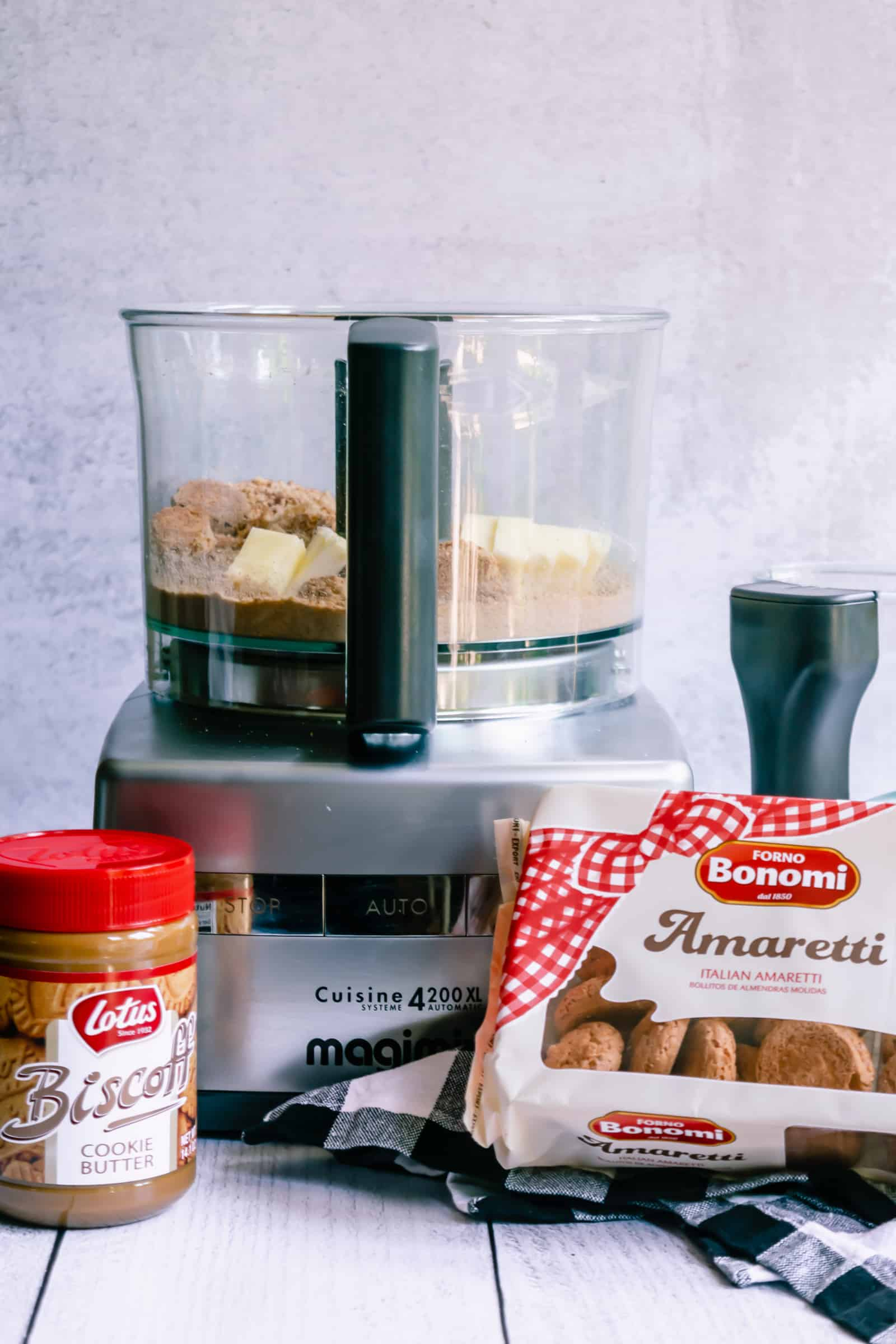food processor with amaretti cookie crumbs, butter and cookie butter and a black and white checked napkin