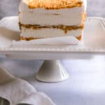 Italian Ice Cream Cake with Cookie Butter and Caramel on a cake stand with a white napkin