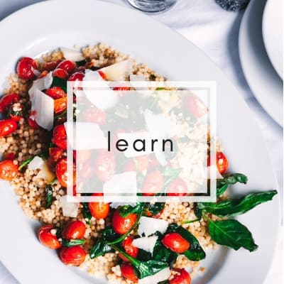 white platter of italian couscous with tomatoes with word learn in a white box