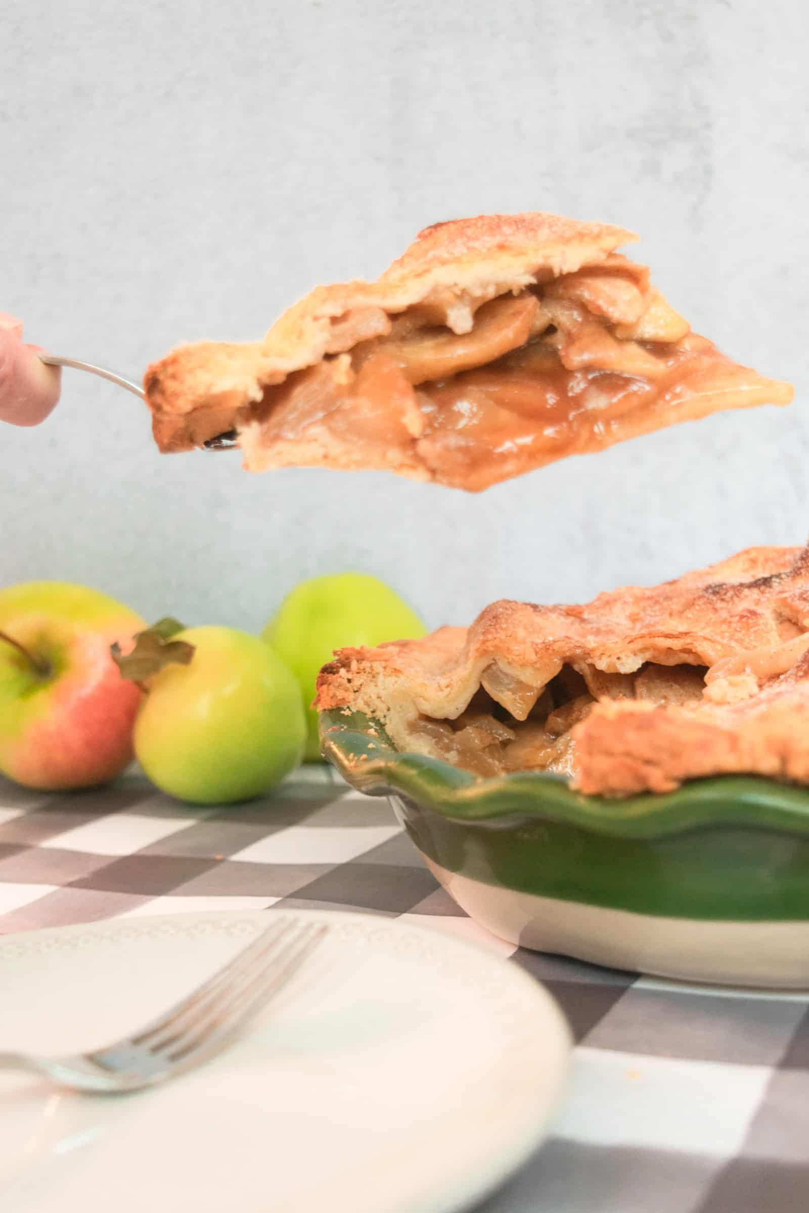 piece of apple pie being served out of a green ruffled edge pie plate with some apples in the background and a gray and white tablecloth and an empty white plate and fork