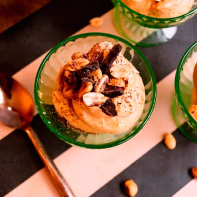 close up of a green bowl of peanut butter mousse topped with chopped chocolate and peanuts on a black and brown striped runner with a copper spoon