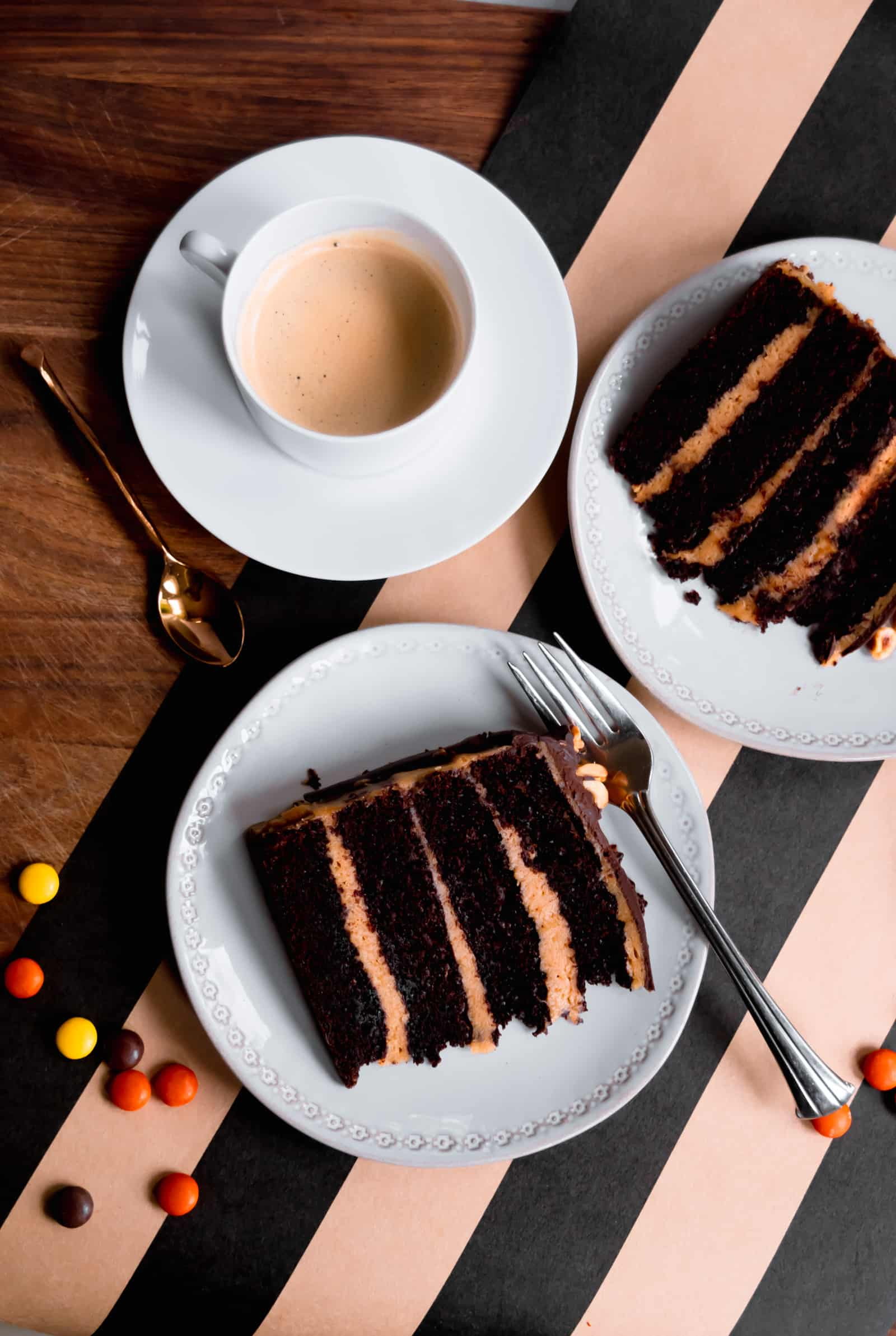overhead of two pieces of four layer chocolate cake with peanut butter mousse filling and a cup of coffee on a black and brown striped runner with reese's pieces sprinkled on it