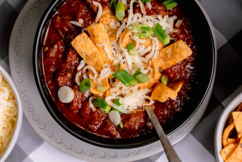 zoom shot of chili topped with fritos, cheese and green onions in a black bowl on a gray plate