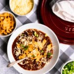white bowl of steak chili with bowls of green onions, white grated cheddar and fritos on a gray and white checked runner