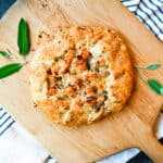 butternut squash and gruyere crostata on a wooden pizza peel with fresh sage leaves on a white dish towel with black skinny stripes