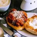 meatball sandwich on a roll with a black and white gingham napkin, silverware and a bowl of parmesan on a dark background