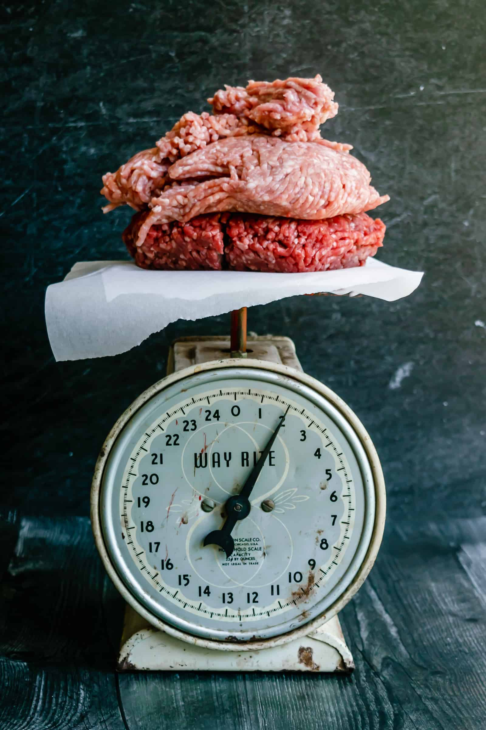 old fashioned scale set on a dark background with homemade meatball ingredients like ground beef and pork