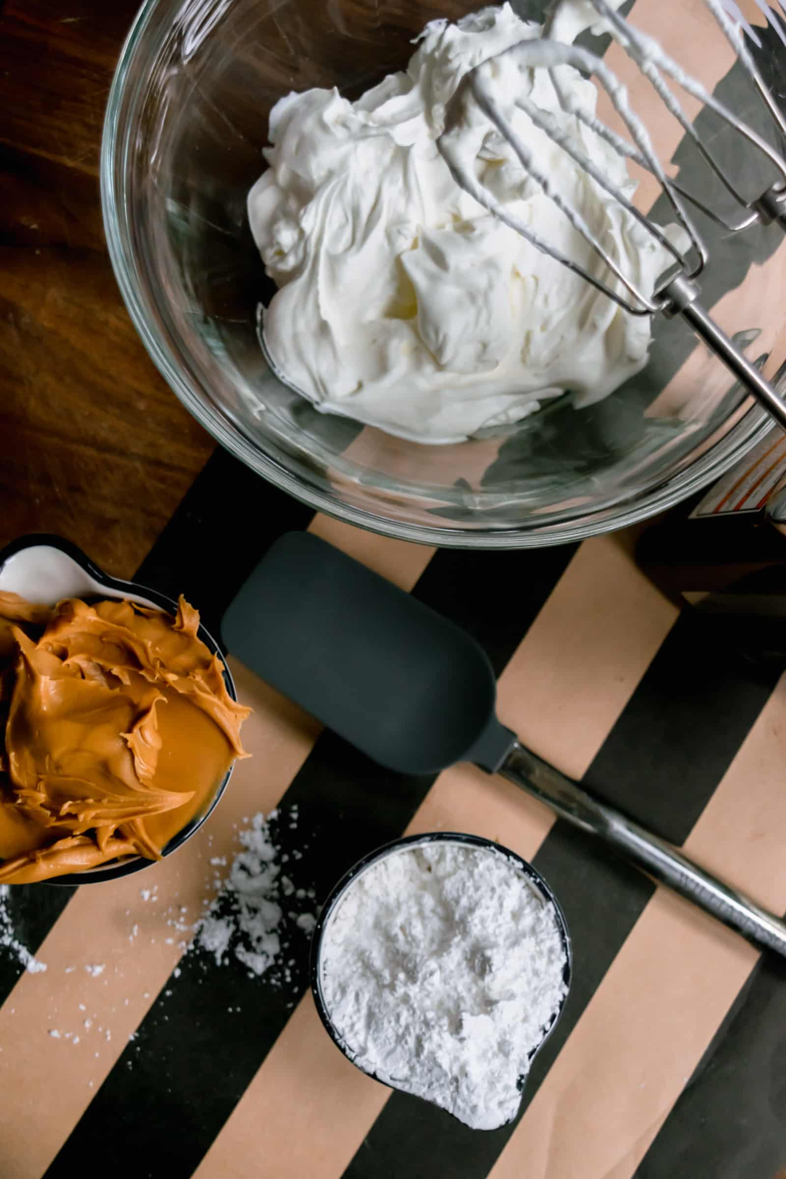whipped heavy cream in a glass bowl with mixer beaters and a small cup of peanut butter and a small cup of powdered sugar and a black spatula on a black and brown striped runner