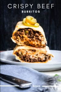 Pinterest image of stacked crispy beef burritos on a white plate and a dark background