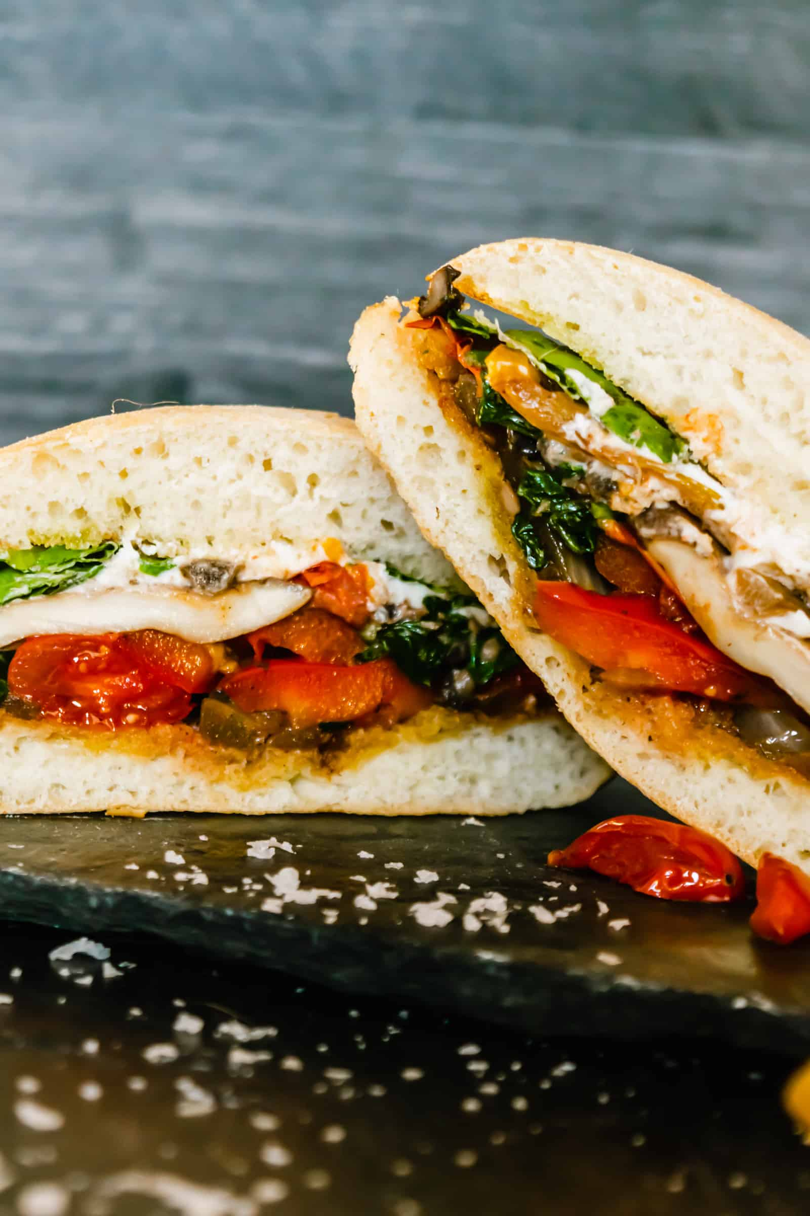 two halves of veggie sandwich facing forward one angled on top of the other on a slate board