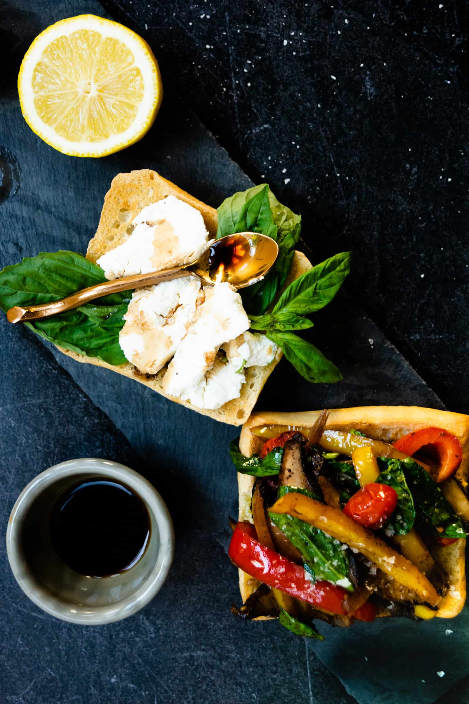 open faced veggie sandwich with goat cheese spread on one half and a gold spoon over top with a small bowl of balsamic