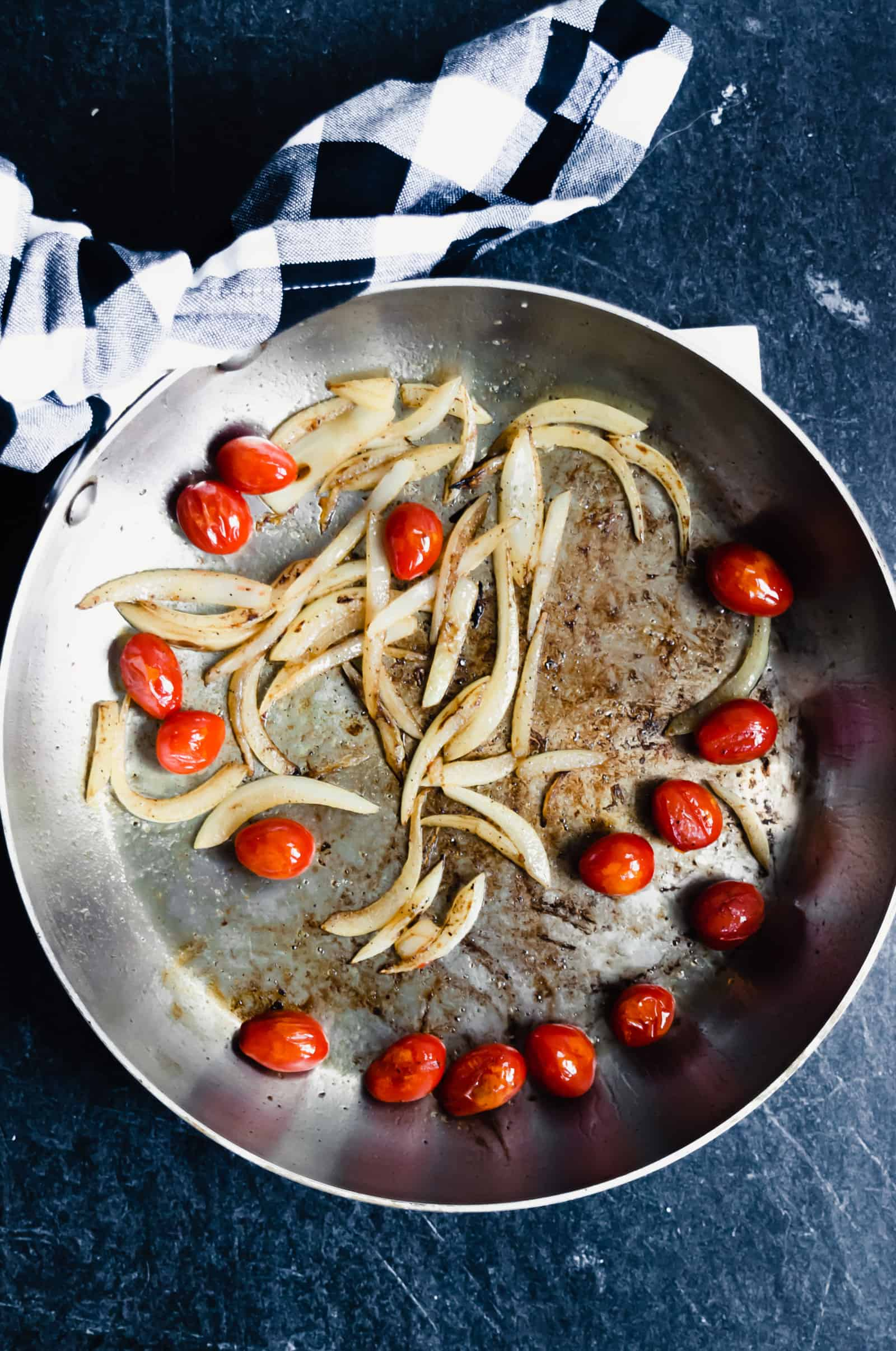 cherry tomatoes and onions sauteed in a stainless skillet with a gingham napkin tied on the handle