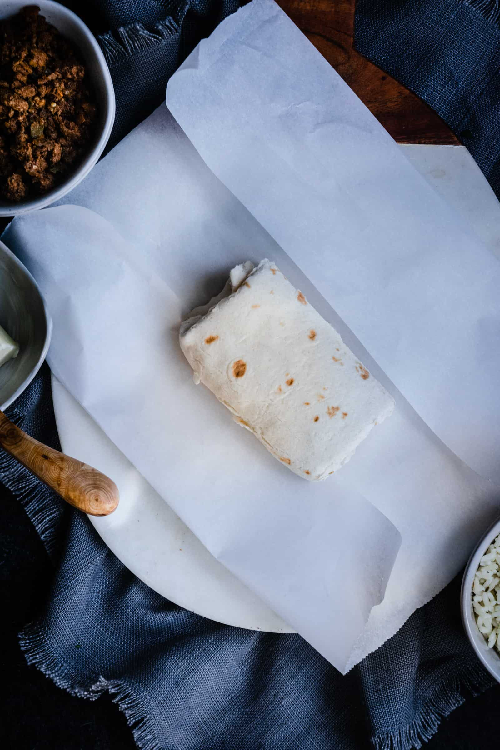 burrito on with top and bottom edges of parchment paper folded