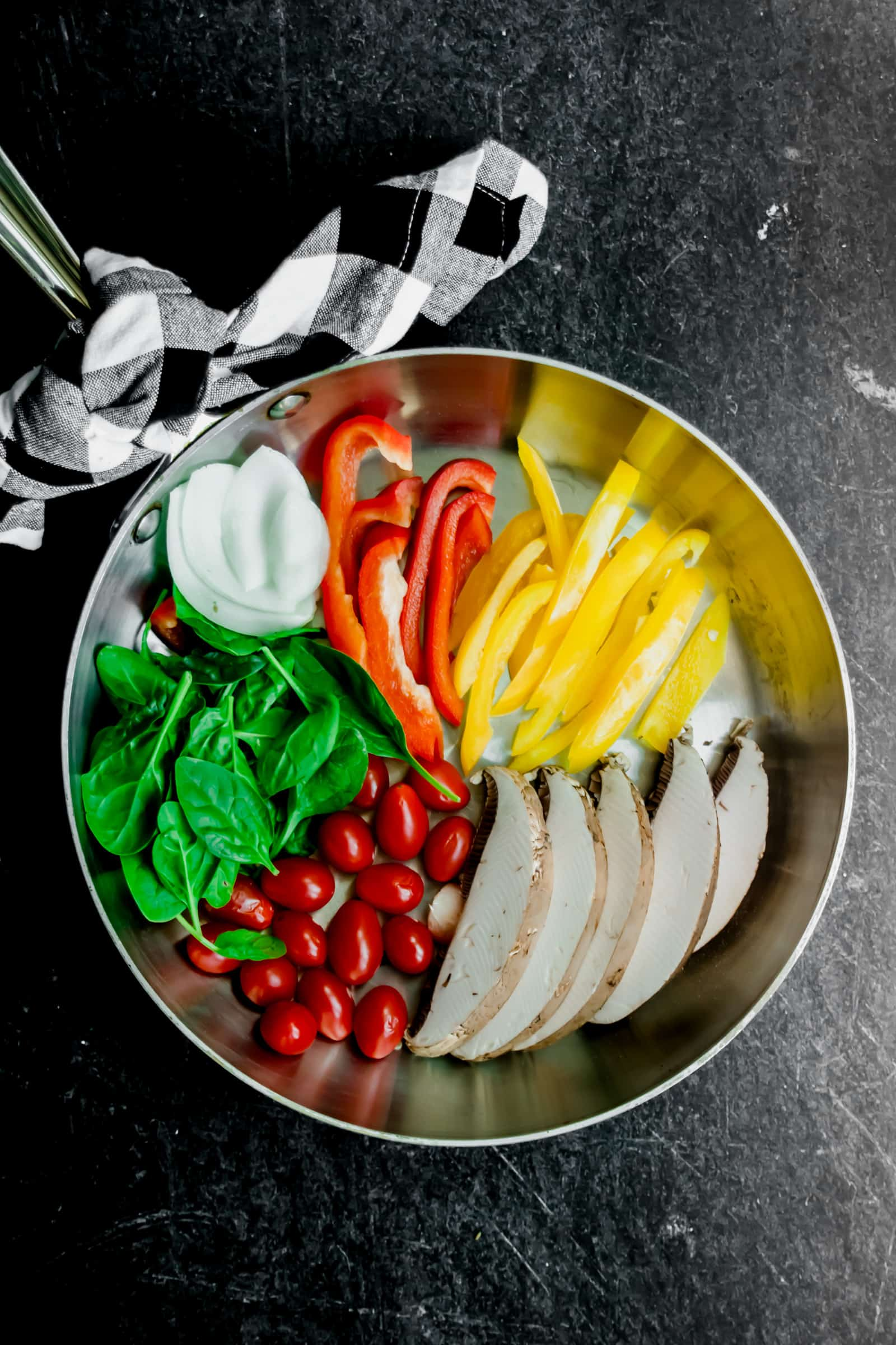 Raw veggies in a stainless skillet with a gingham napkin tied on the handle on a black background