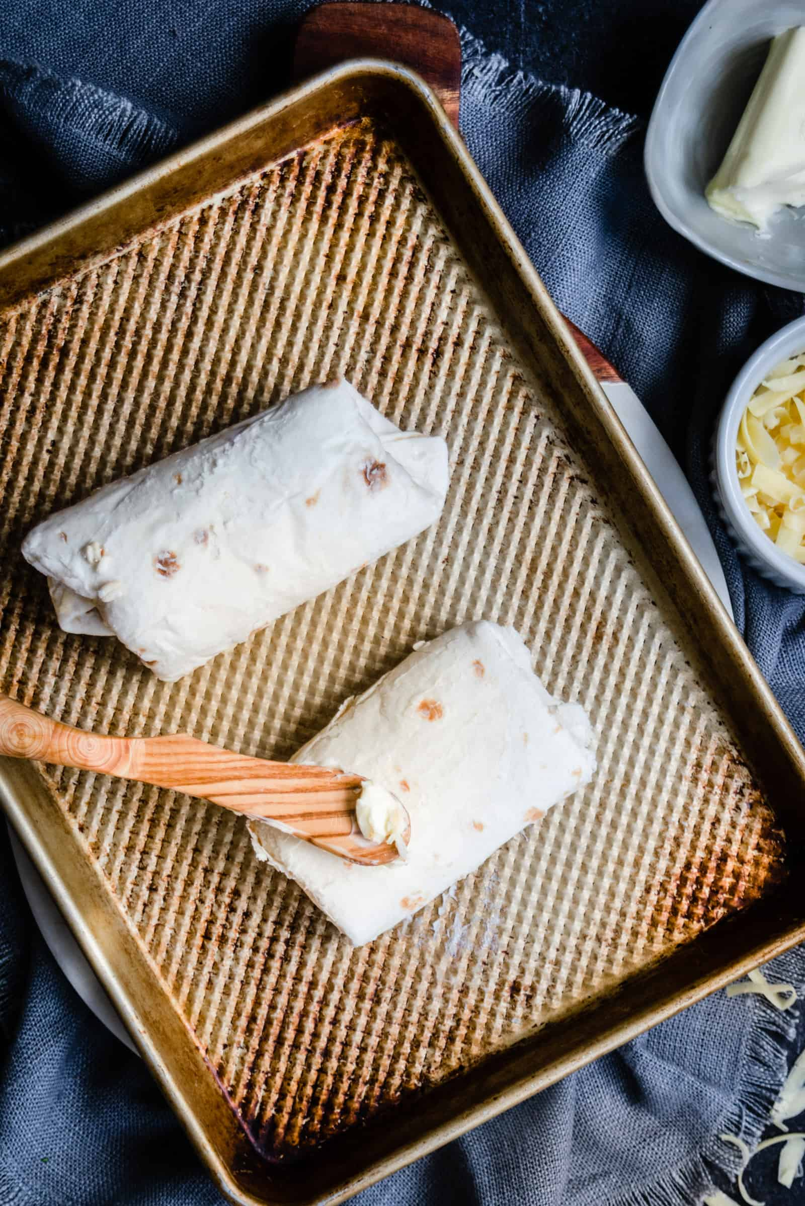 two buttered burritos with a spreader on a baking sheet with a gray blue napkin and bowl of butter nearby