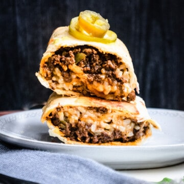 close up of two burritos stacked on top of each other with pickled jalapenos on top all on a white plate and some cilantro