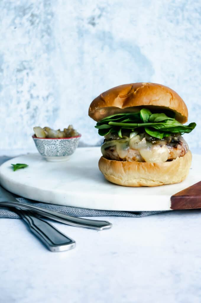 turkey burger on a white marble board with utensils and a bowl of caramelized onions to the side