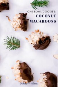 marble background with chocolate dipped coconut macaroons scattered on it with some small pieces of pine