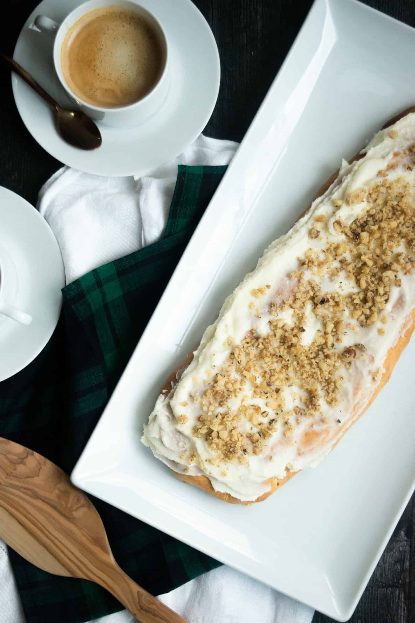 Danish puff pastry on a white platter with a cup of coffee in the background on a blackwatch plaid napkin and white runner with a black background