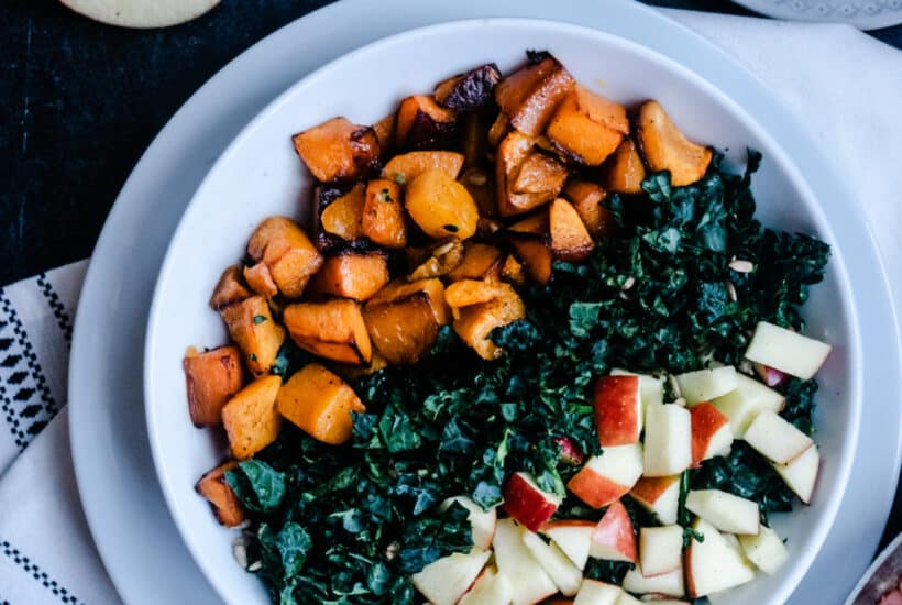 Butternut Squash, Juici Apples and Chopped Kale topped with Warm Pancetta Dressing with pasta in a white bowl on a dark background with a white napkin and some apples and a skillet of pancetta