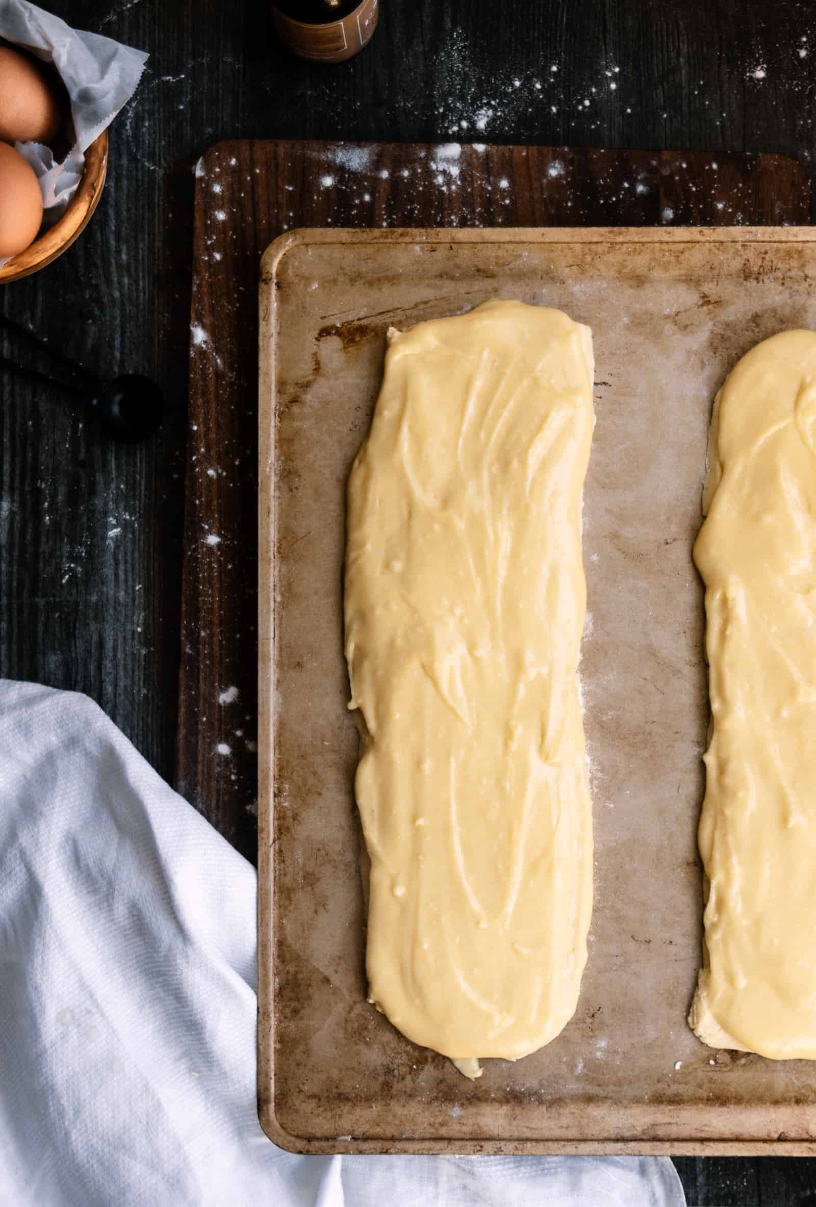 two strips of Danish Puff Pastry on a baking sheet and dark cutting board on a a black background and white napkin