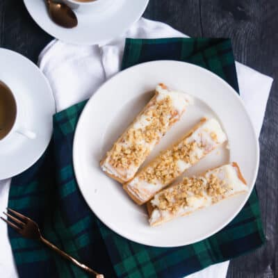 three pieces of Danish puff pastry on a white plate with two cups of coffee in the background on a blackwatch plaid napkin and white runner with a black background