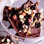 close up of pieces of dark chocolate espresso bark with cherries, pistachio and hazelnuts on a glass pedestal