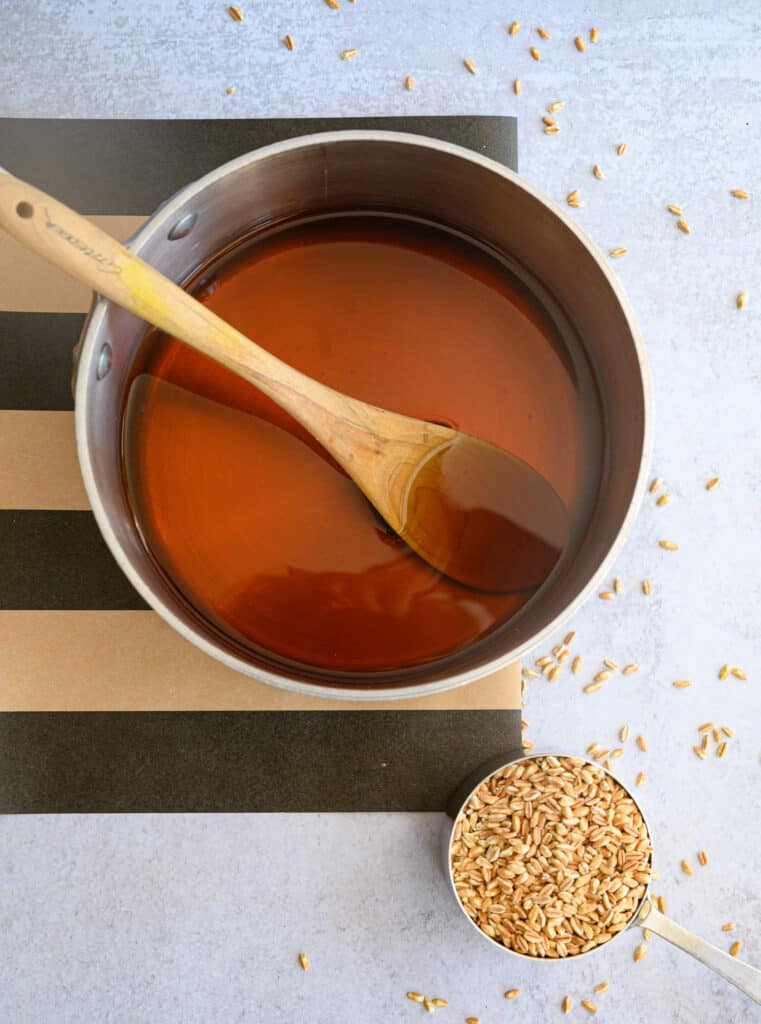 broth in a saucepan with a wooden spoon and a cup of farro in a measuring cup on a black and khaki striped runner