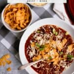 Bowl of Steak Chili with corn chips and cheese on top on a gray and white checked background
