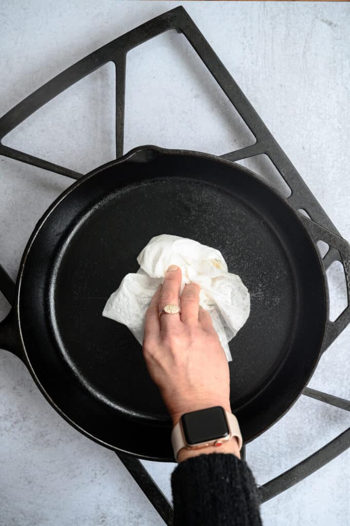 hand holding a paper towel oiling a cast iron skillet that is on a grate