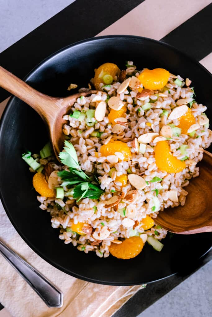 a black bowl with farro and orange salad with two wooden spoons on a black and khaki striped background