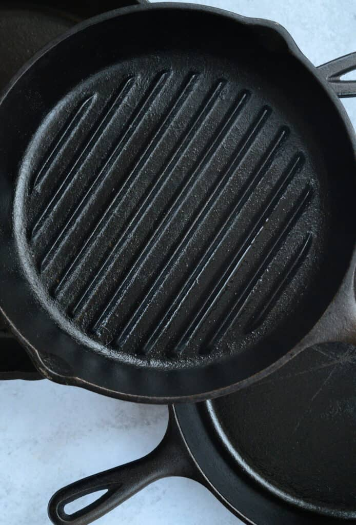 overhead shot of stack of cast iron skillets and grill pans