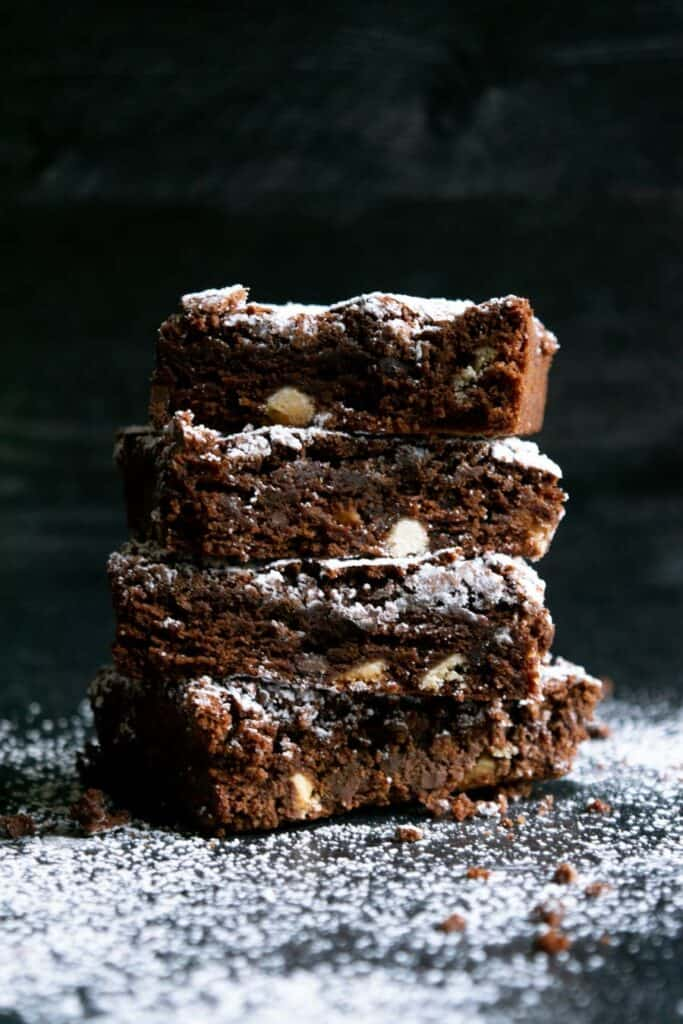 three stacked triple chocolate brownies on a dark background sprinkled with powdered sugar