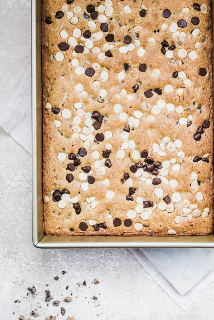 pan of chocolate chip blondies on a cream background with some toffee chips