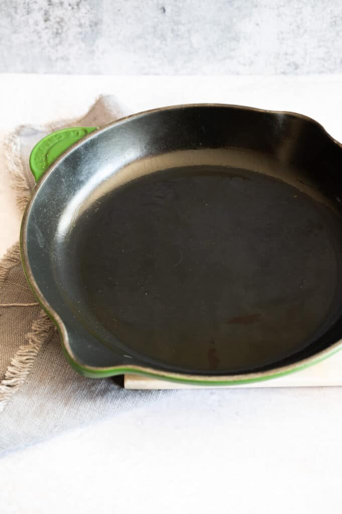 heated green cast iron skillet with oil in it