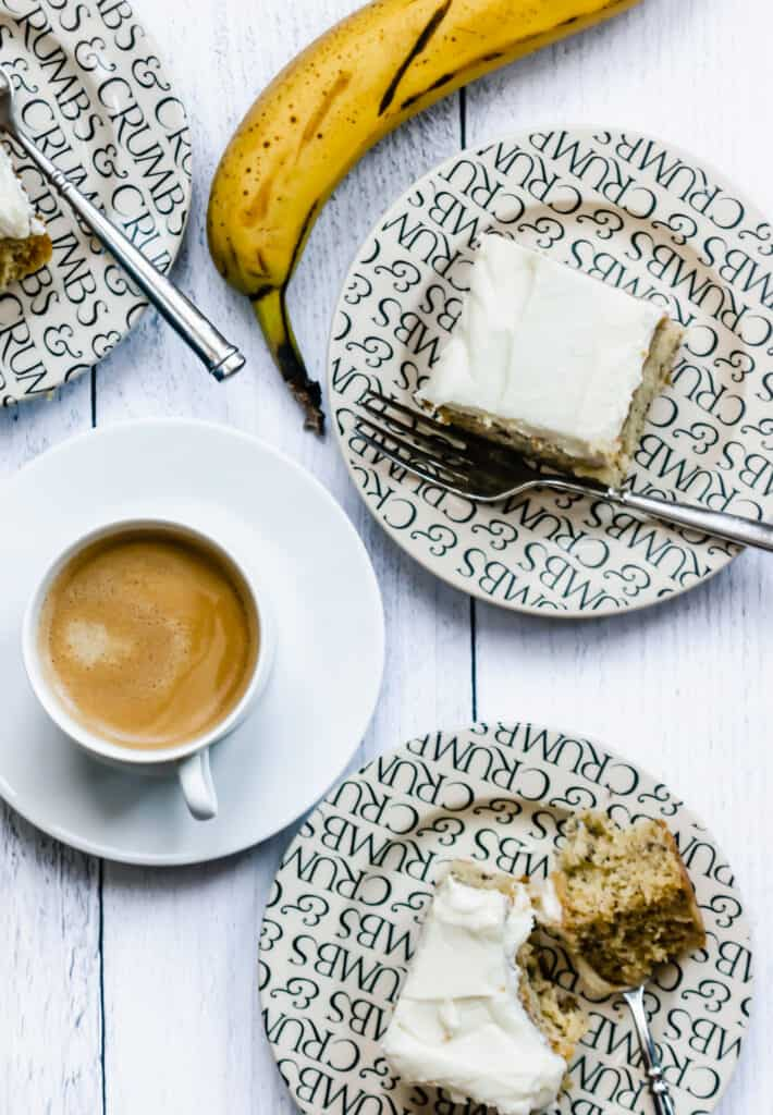 overhead shot of frosted banana sheet cake pieces on plates with a cup of coffee