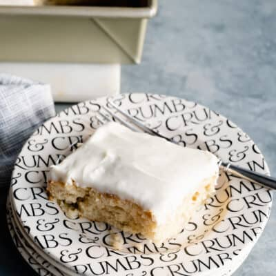 piece of banana sheet cake on a black and white plate with a fork