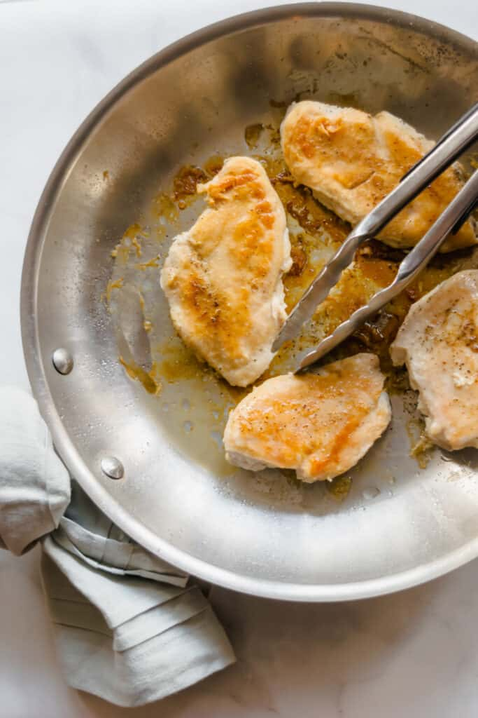 pan of seared and cooked chicken breasts with a tong and blue napkin tied to the handle