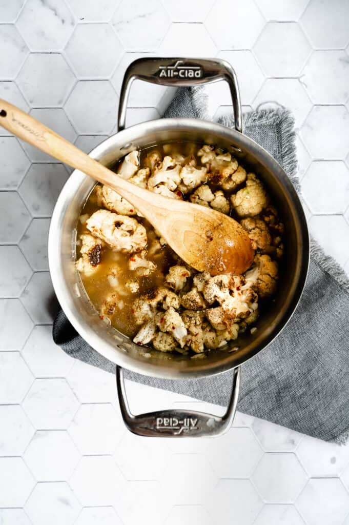 soup pot of roasted cauliflower, seasoning and broth with a wooden spoon on a gray napkin and a marble hexagon tile background